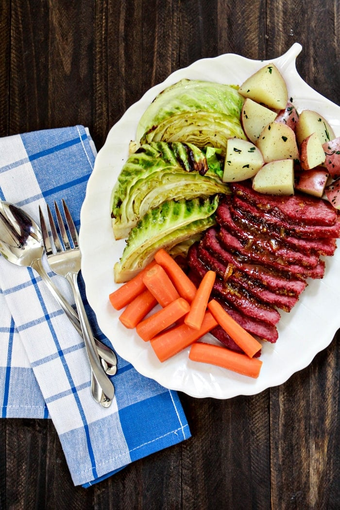sliced baked corned beef with mustard and brown sugar on plate with potatoes, carrots, and cabbage