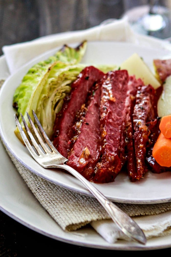 slices of oven baked corn beef with vegetables on plate