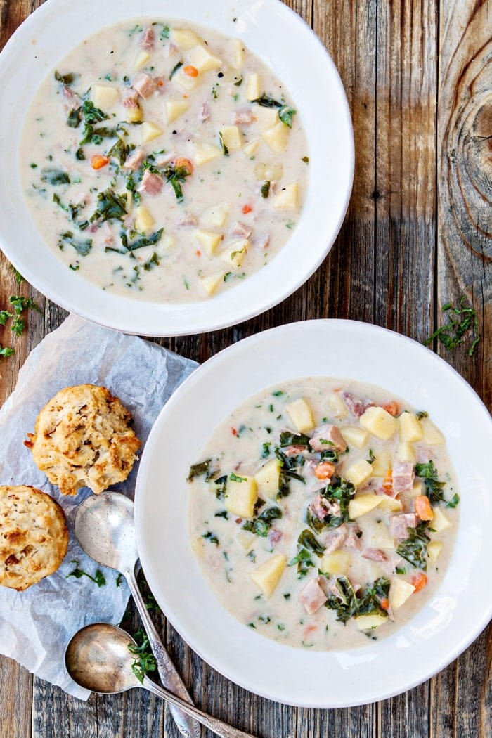 Slow Cooker Ham Soup with Potatoes and Kale in white bowls with beer bread muffins