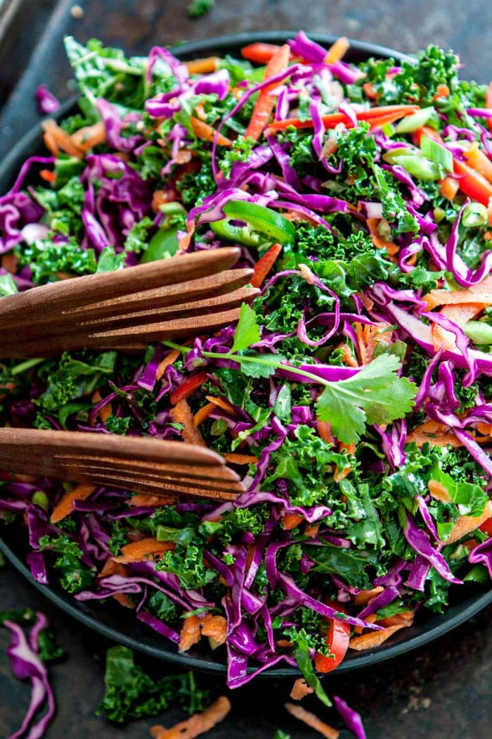 Cilantro Lime Slaw in serving bowl with wooden salad tongs