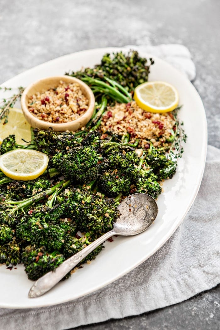 roasted broccolini on white serving platter with lemon slices and bread crumbs