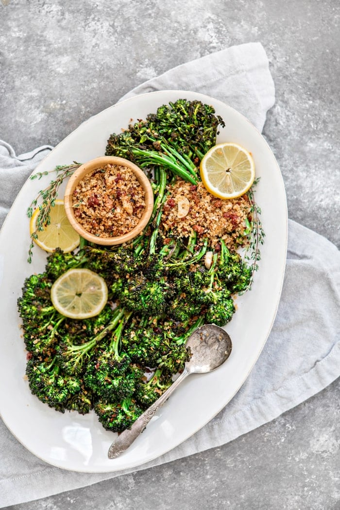 roasted broccolini on a white serving platter with lemon slices and panko bread crumbs