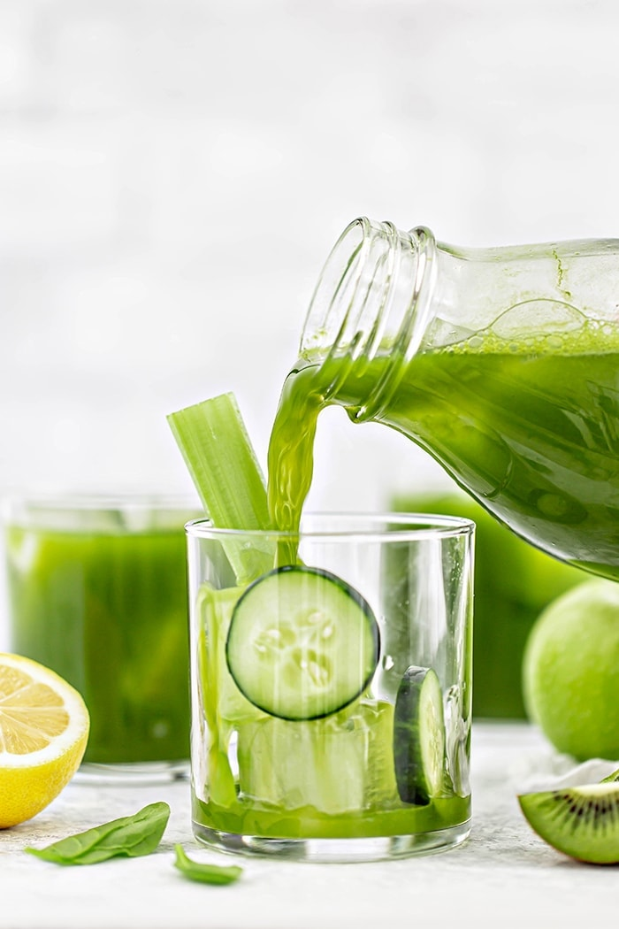 green juice pouring into a glass with cucumber slices and ice cubes
