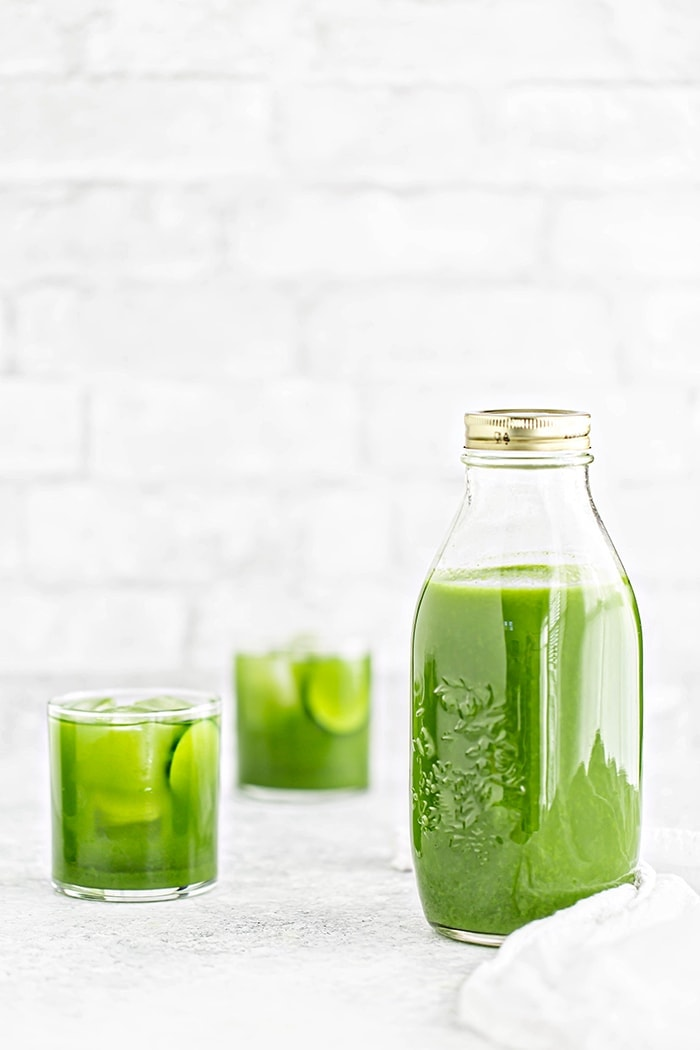 a jar of green juice and two glasses with ice and green juice