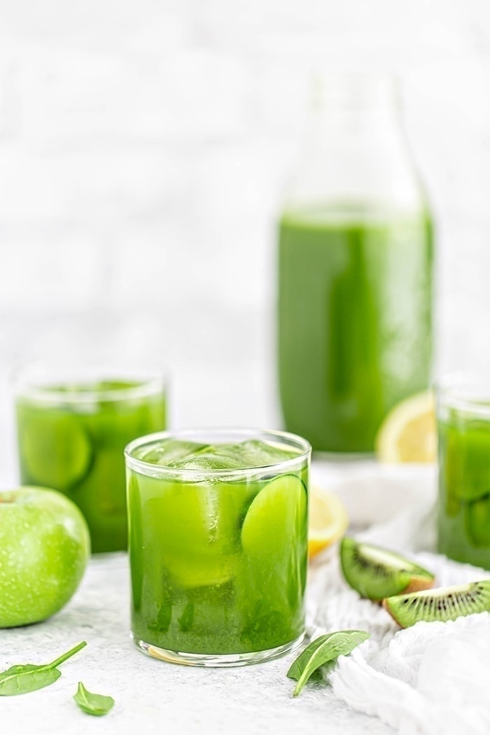 3 glasses of green juice with apples, spinach, lemon, cucumber, and kiwi