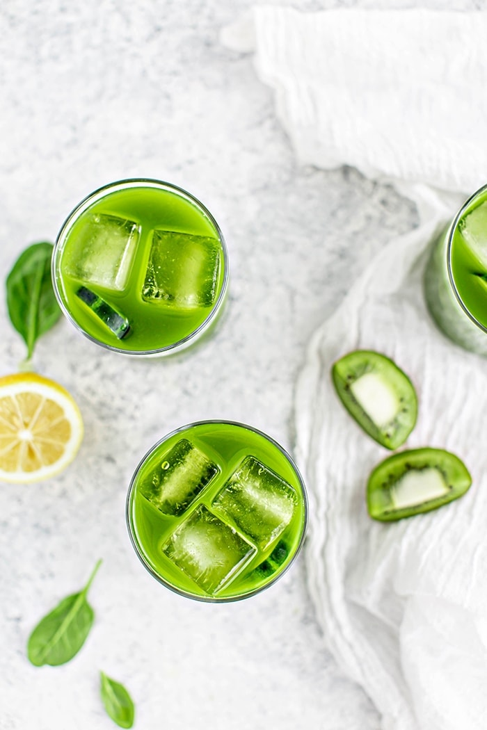 overhead image of 3 glasses with spinach juice on a white background