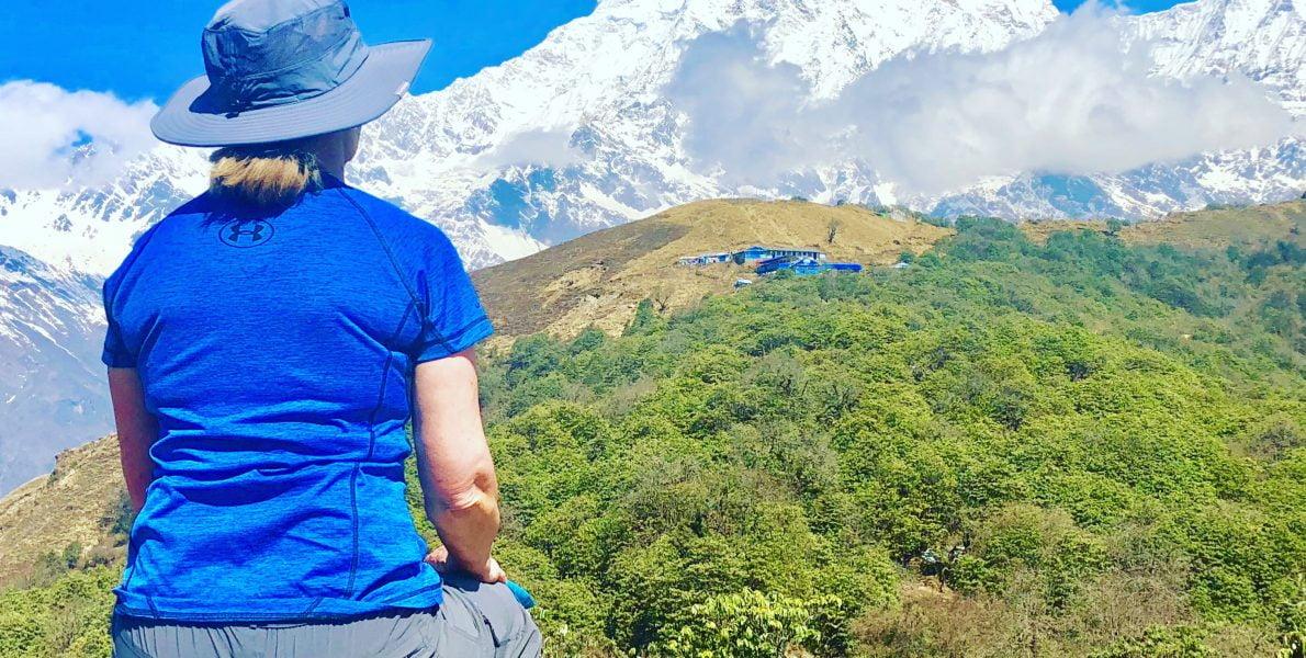 A women sitting on a chair facing Annapurna mountains in Australian Base Camp