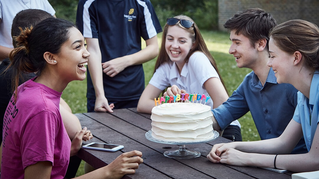 A group of student celebrating a birthday with a cake