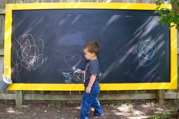 toddler coloring on an outdoor chalkboard
