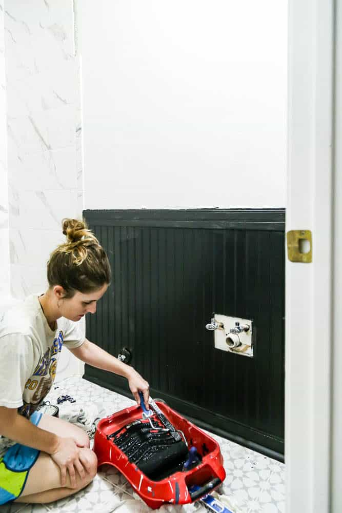 woman painting beadboard paneling in bathroom white