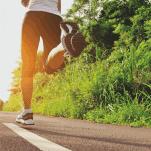 female runner on country road running in morning