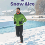 male running in snow next to a body of water