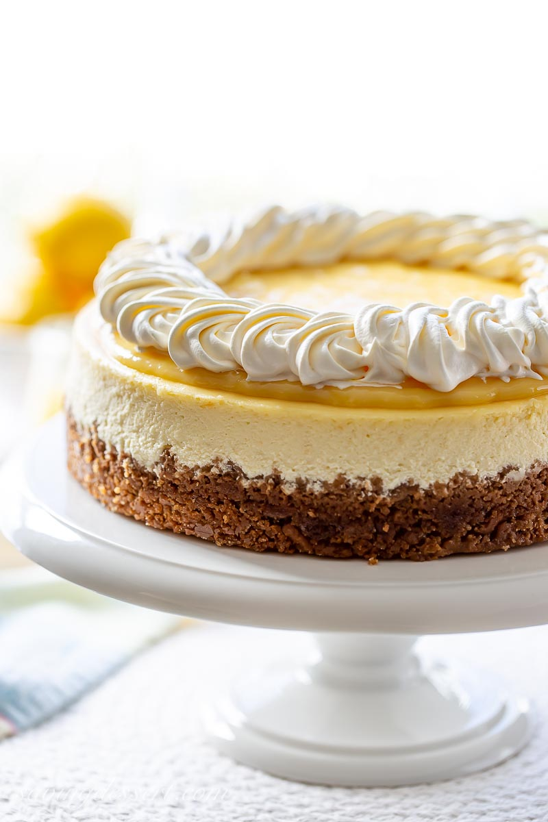 A lemon cheesecake with a graham cracker crust on a cake stand