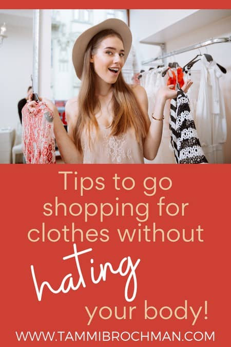 woman picking out clothing while smiling, tips to go shopping for clothes without hating your body