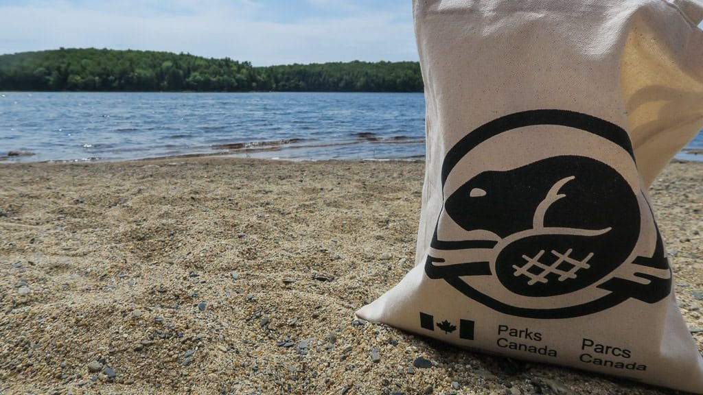 Parks Canada bag sitting on the sand at a beach in kejimkujik national park