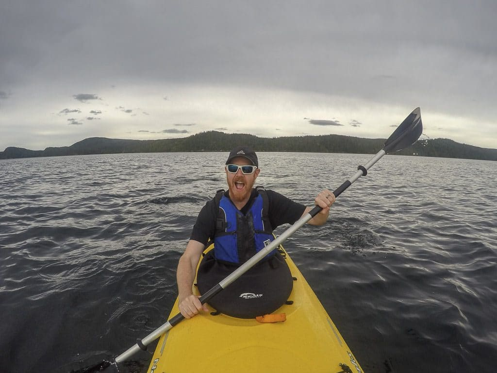 Buddy paddling in the waters of Terra Nova National Park on a very cloudy and gloomy day
