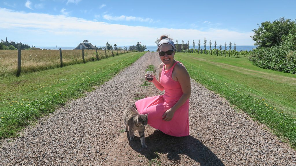 Brooke making friends with a cat at Rossignol Estate Winery while sipping a glass of local wine.