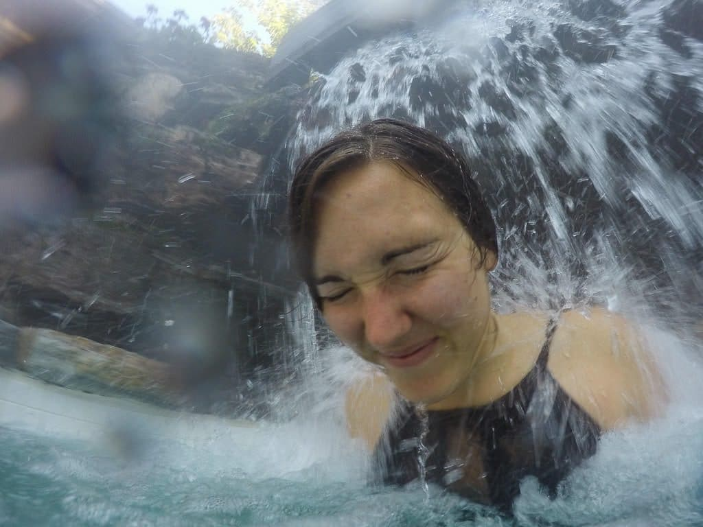 Brooke letting the water pressure from the waterfall beat down on her shoulders to help alleviate the pent-up stress at scandinave spa in mont-tremblant
