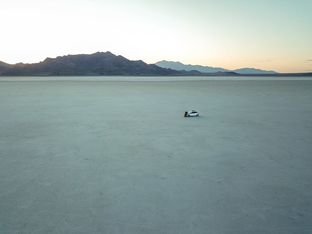 Drone shot of Brooke and Buddy leaning up against the Subaru at the Bonneville Salt Flats with no-one around them