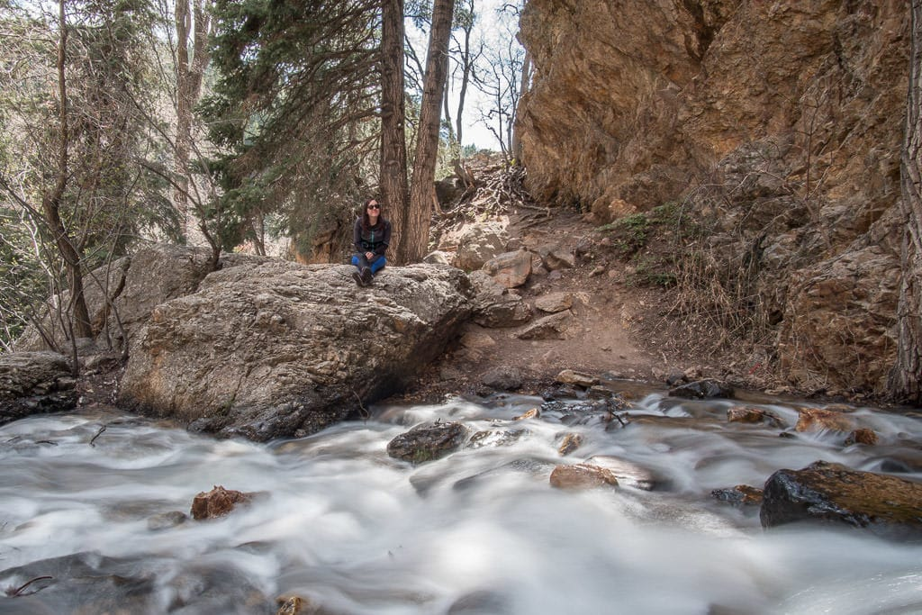 Brooke sitting atop a rock next to the river that flows from Hidden Falls