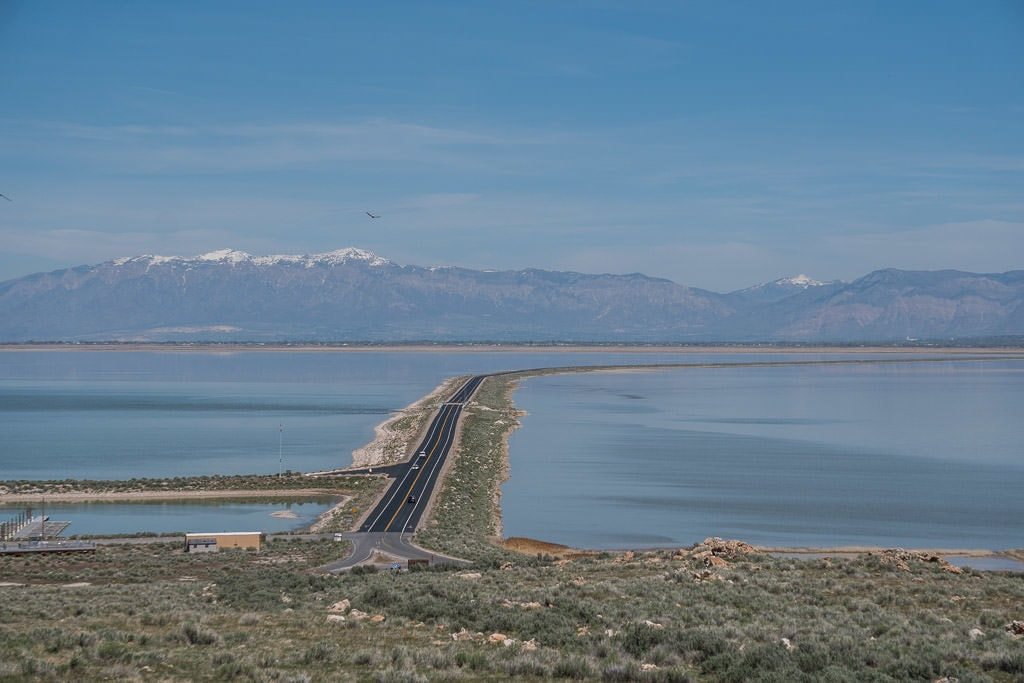 The long causeway to Antelope Island State Park with water on both sides and mountains in the background