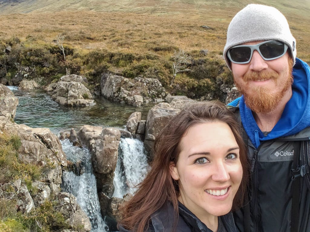 Brooke and Buddy next to a waterfall at Fairy Pools in Isle of Skye
