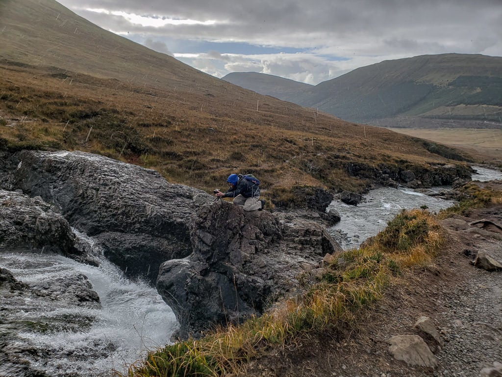 Buddy kneeling on a rock overlooking a waterfall as he takes a photo in the heavy rain during our visit to Fairy Pools in Isle of Skye