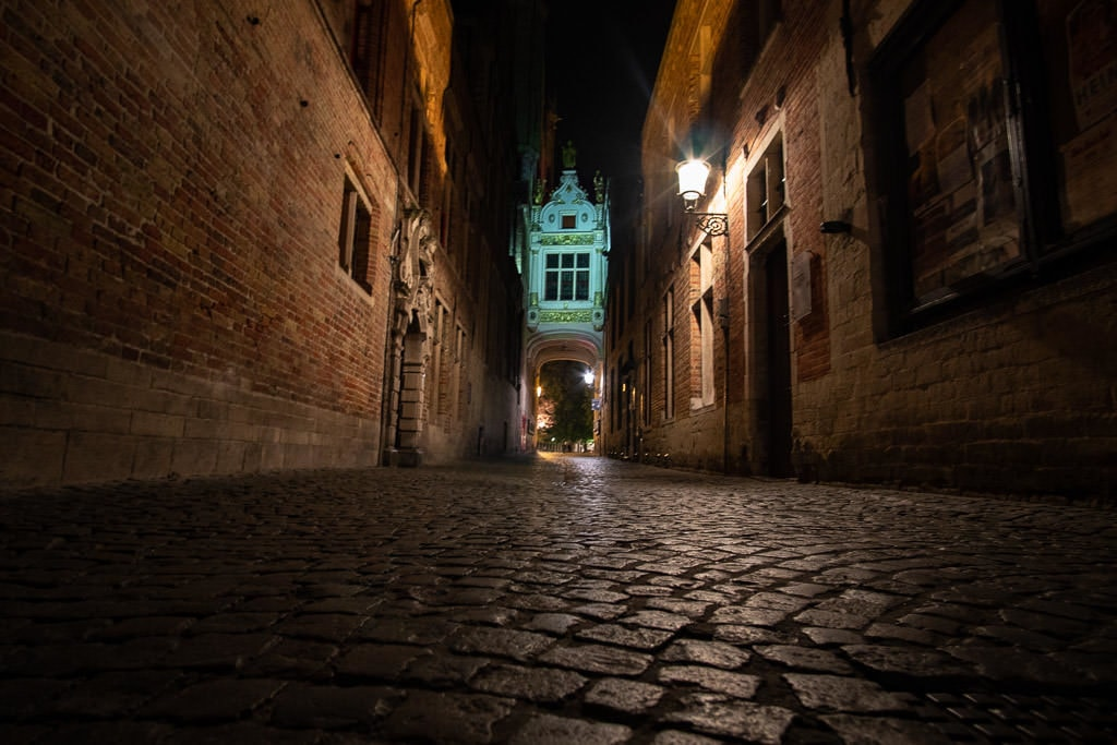cobblestone sidewalk at night in bruges belgium
