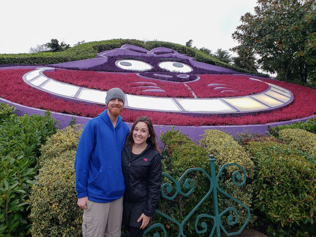 Brooke and Buddy in front of the Cheshire Cat flower garden in the Alice in Wonderland area of disneyland paris