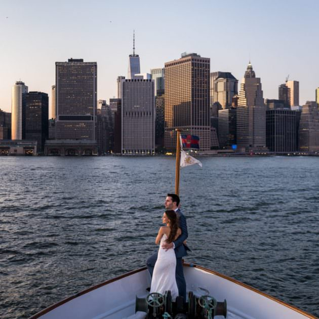 Bride and groom standing side by side on a boat looking off to the distance
