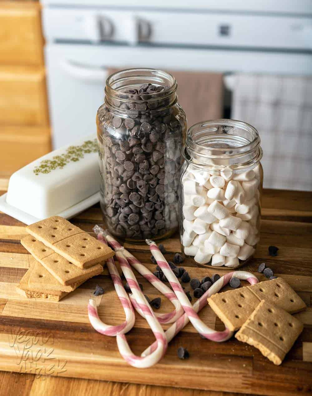 A jars of vegan marshmallows and chocolate chips, near graham crackers, candy canes and a butter dish