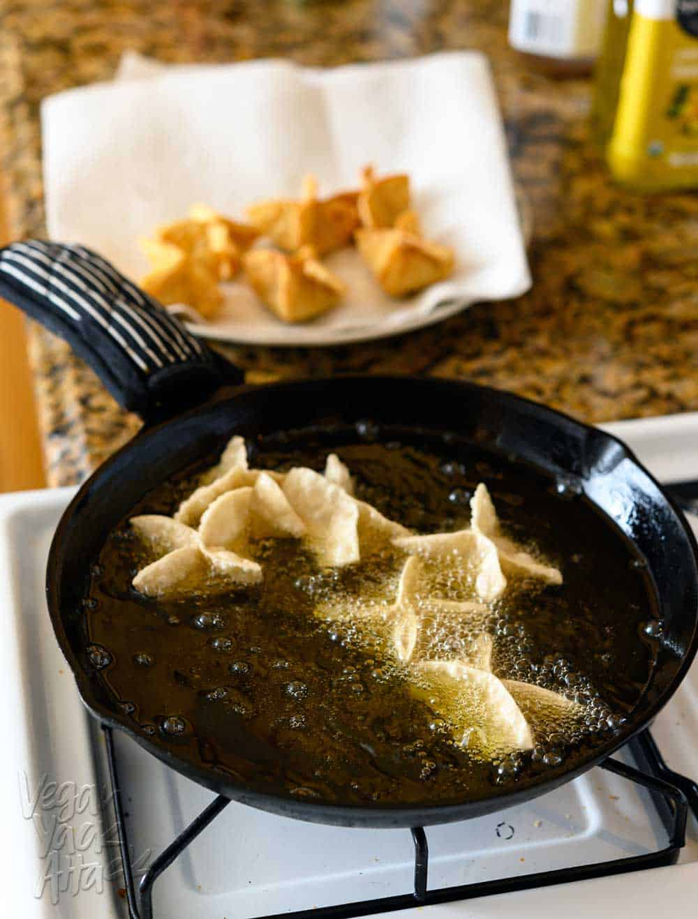 Frying vegan Crab Rangoon in a large, cast iron skillet, on a the stove, with cooked pieces on a plate in the background.