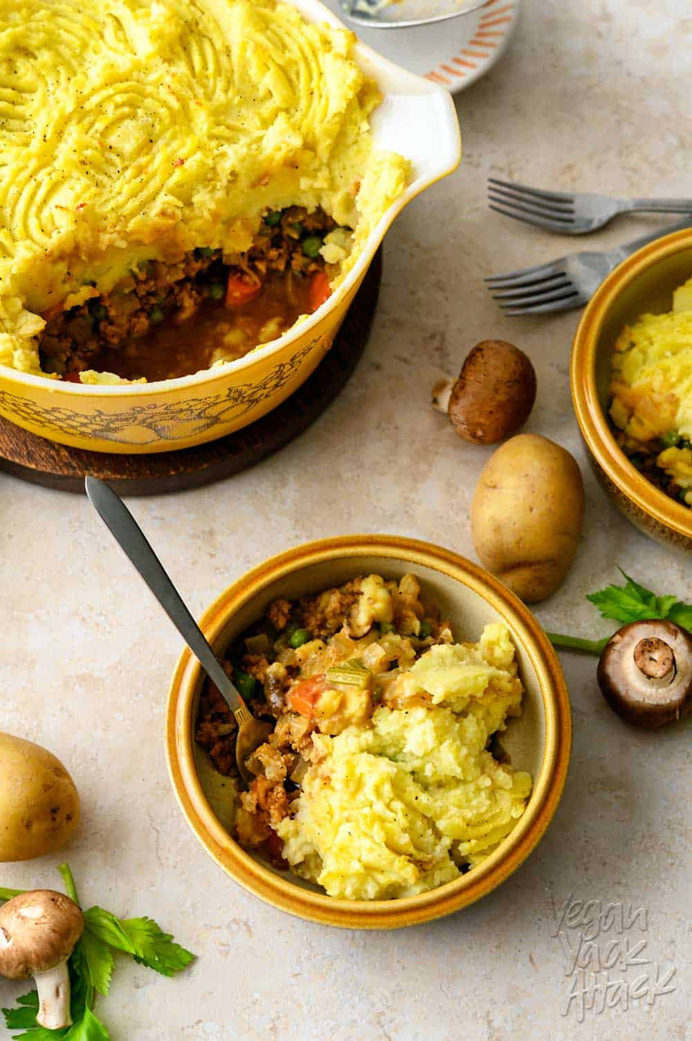 One casserole dish filled with a vegan shepherd's pie, spooned into two bowls, with potatoes and mushrooms scattered around them, on a light linoleum background.