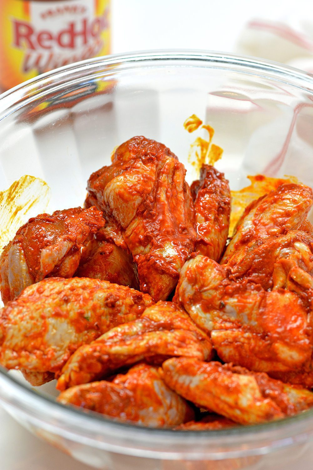 Raw chicken wings covered with buffalo sauce