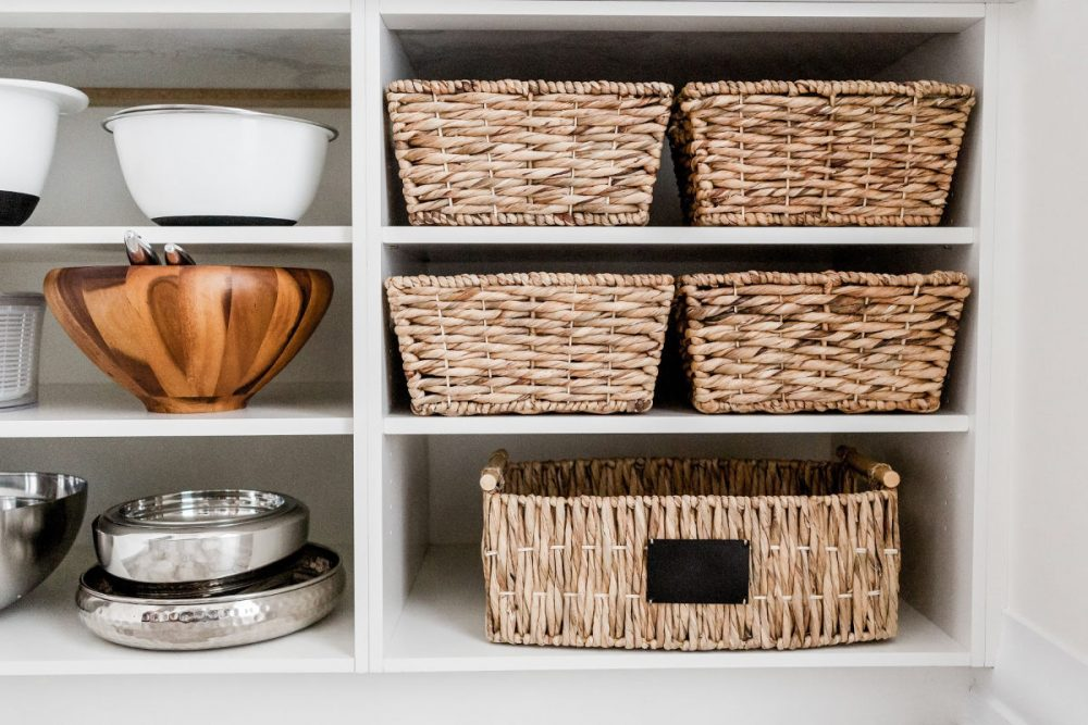 open kitchen cabinet organized with wicker baskets