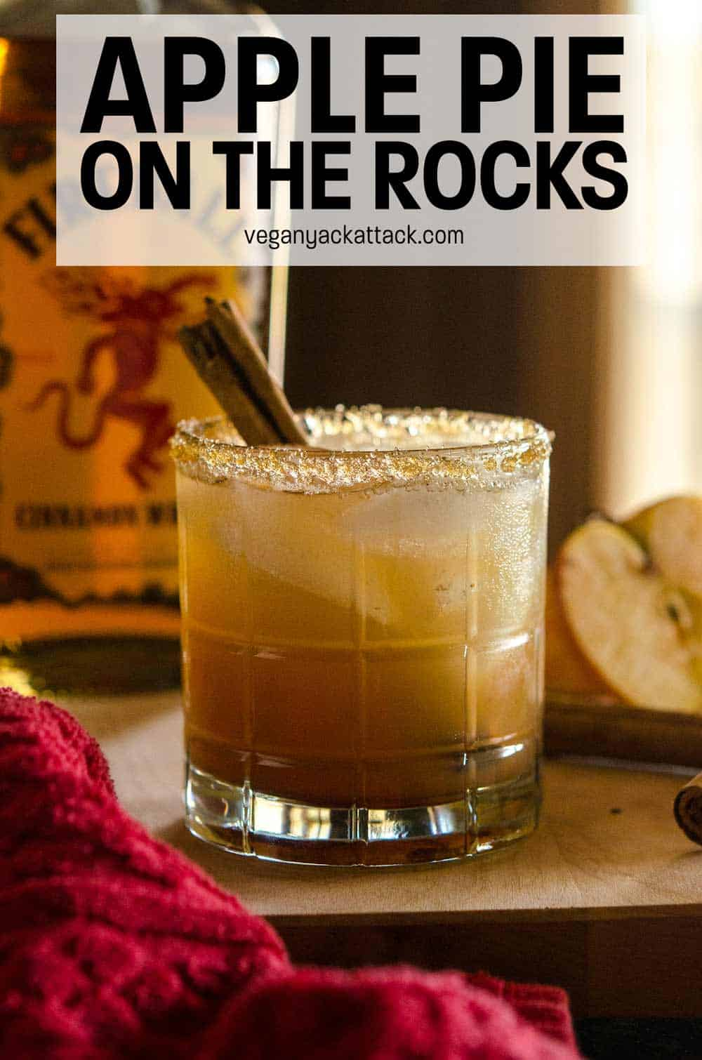 Glass of apple pie on the rocks with sugar rim and cinnamon stick on a cutting board