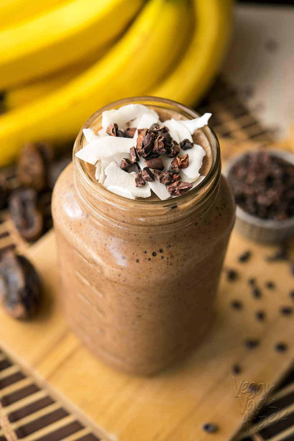 Large jar filled with banana cacao recovery smoothie, on a bread board surrounded by ingredients