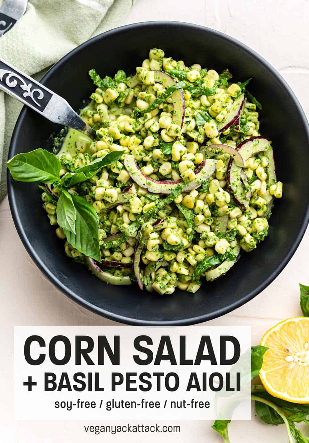 Large black bowl filled with Summer corn salad and basil pesto aioli with tongs and linen nearby