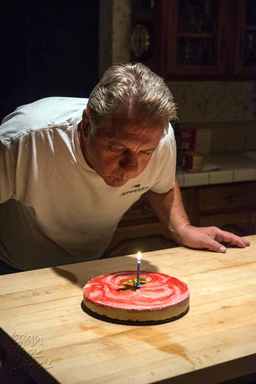 Older gentleman blowing out birthday candle on cheesecake