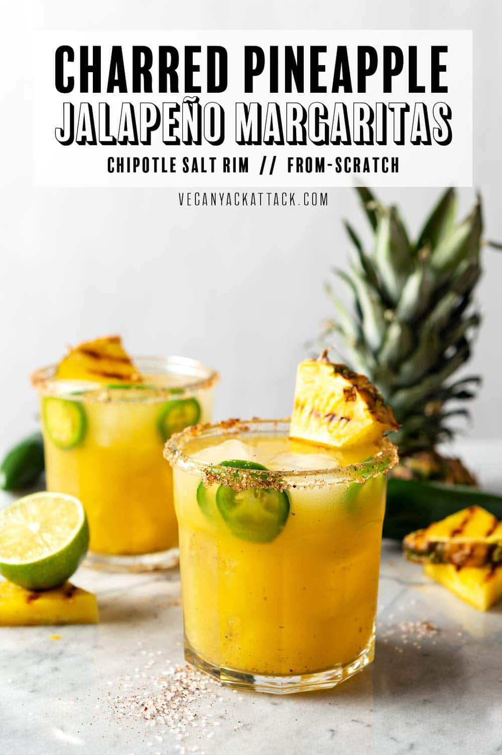 "Two glasses filled with Pineapple Margarita, with fresh jalapeños, grilled pineapple wedge garnish, and chili-salt rim. Text at top reads ""Charred Pineapple Jalapeno Margaritas."""