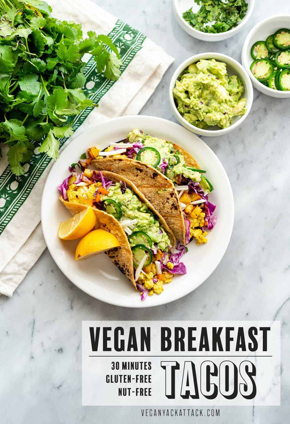 "An image of tacos plated, on a marble table with assorted toppings near it, text reading ""vegan breakfast tacos"""