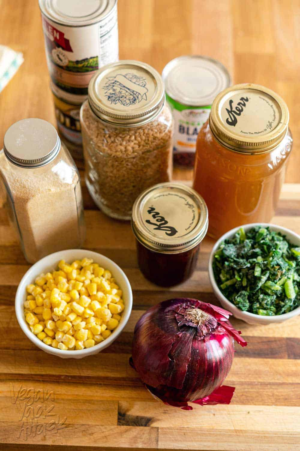 Image of ingredients: red onion, corn, kale, vegetable broth, grains and beans