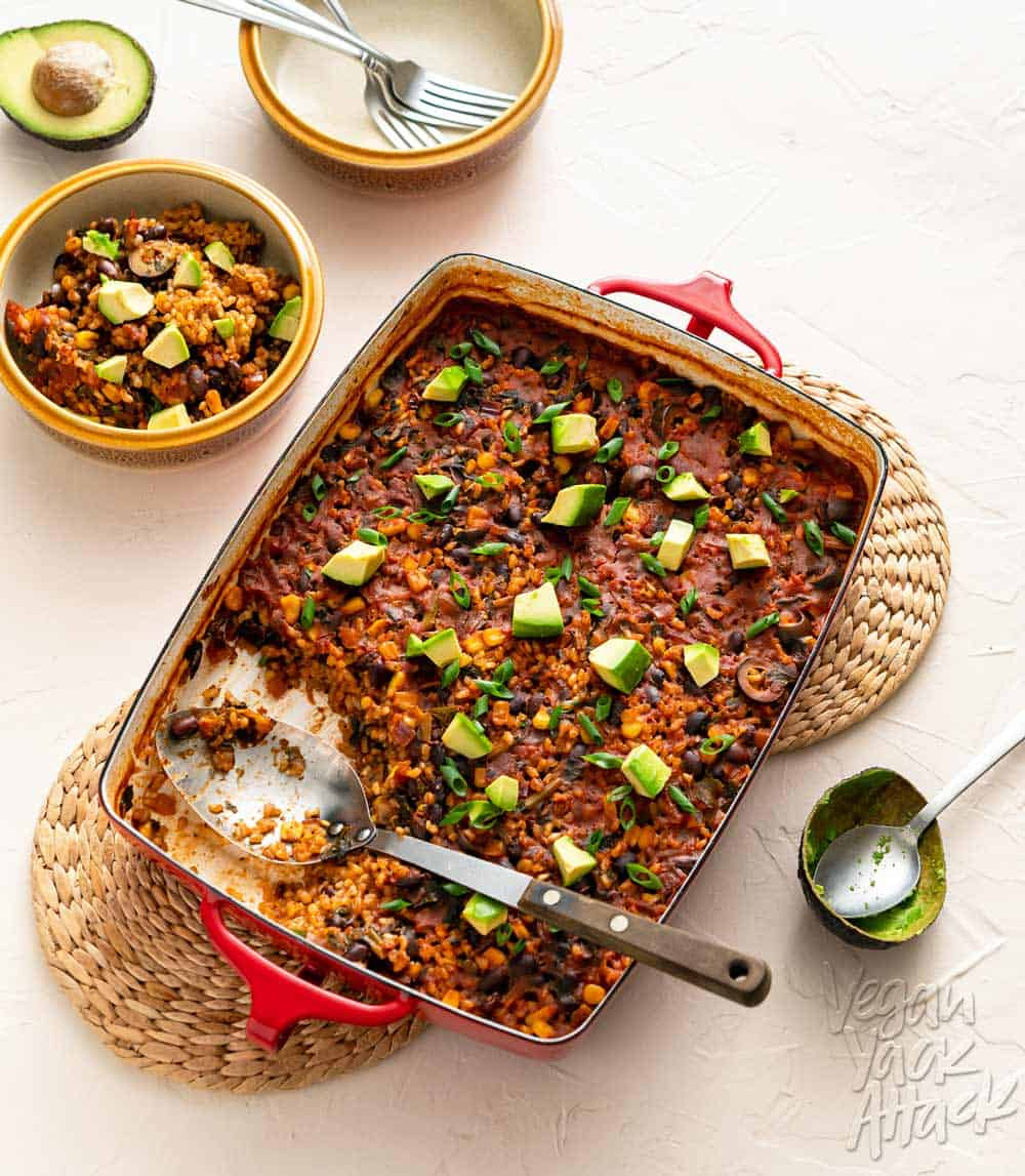 Image of chipotle brown rice bake in a red casserole dish on a beige background