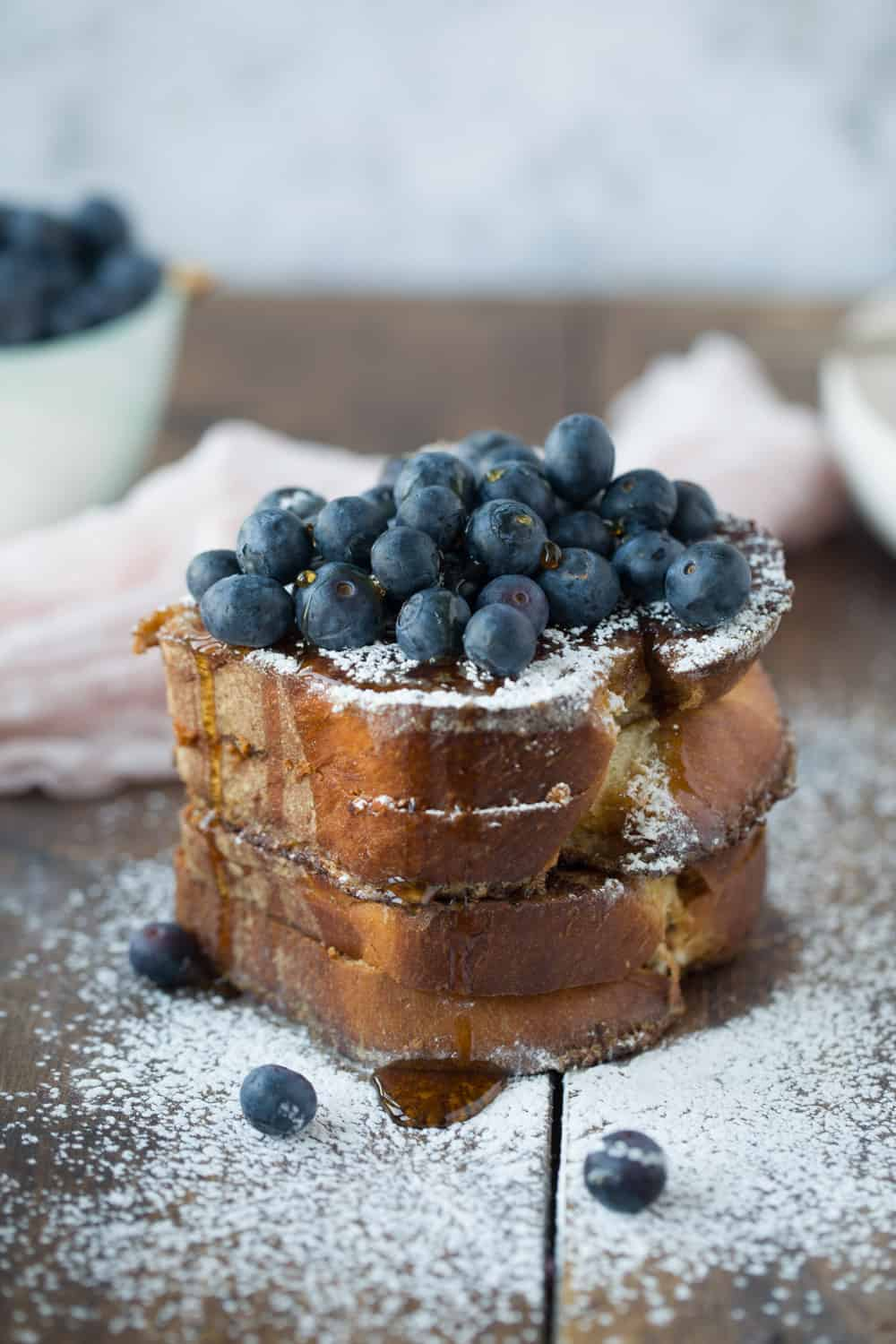 A stack of French toast covered with blueberries, drizzled with maple syrup and sprinkled with powdered sugar