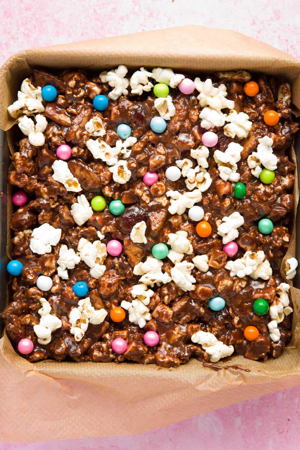 A slab of popcorn rocky road inside a square baking tin.
