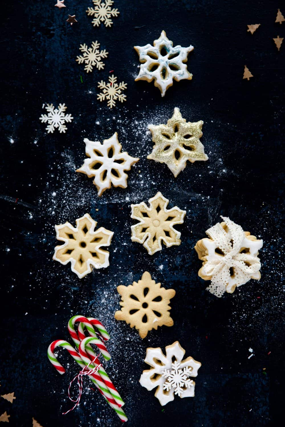 Overhead view of 7 snowflake biscuits on a dark blue background. There is a stack of biscuits to the right and at the bottom of the image a bundle of candy canes.