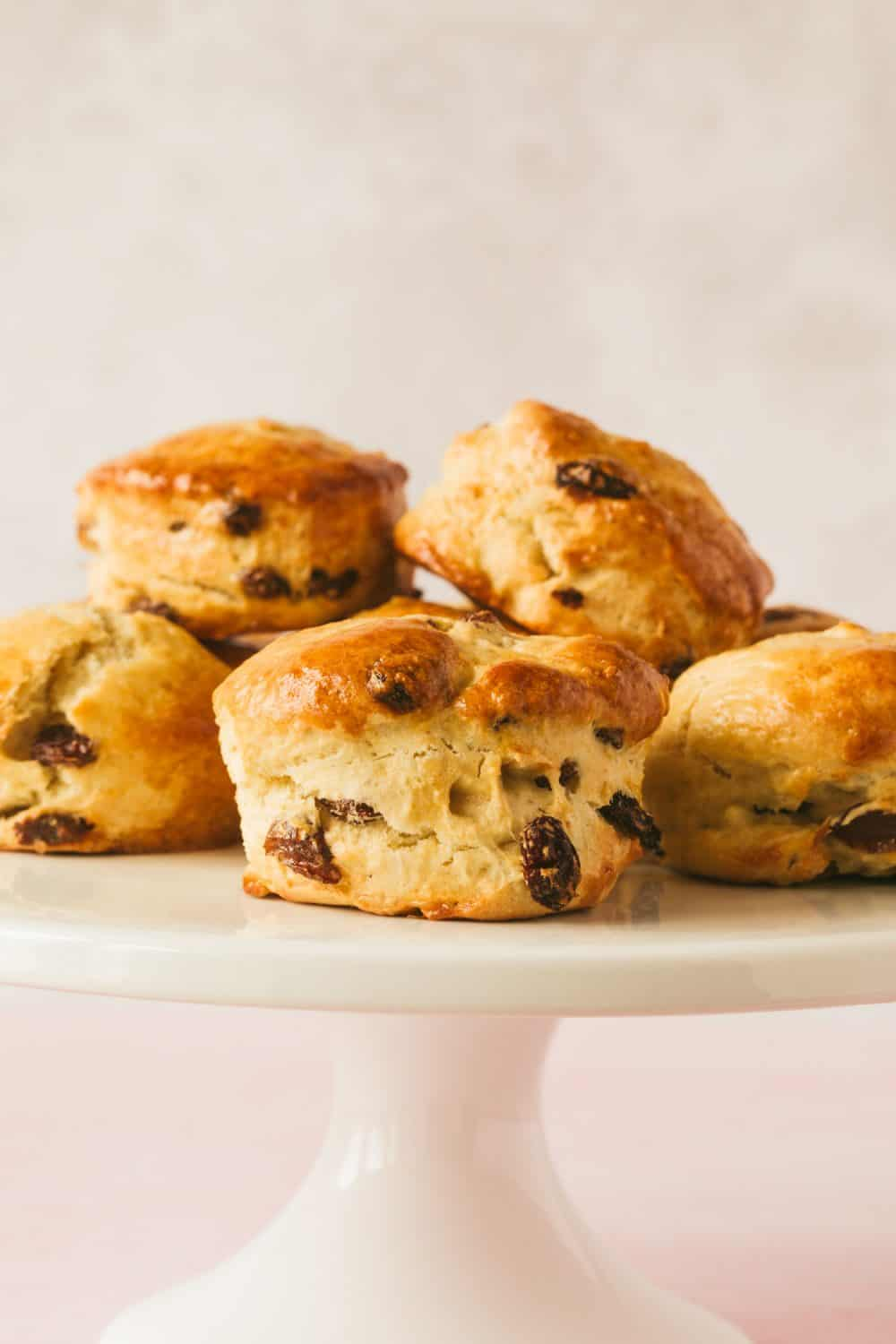 Side view of 6 fruit scones on a white cake stand. There are visible sultanas protruding from the scones and they are golden brown in colour.