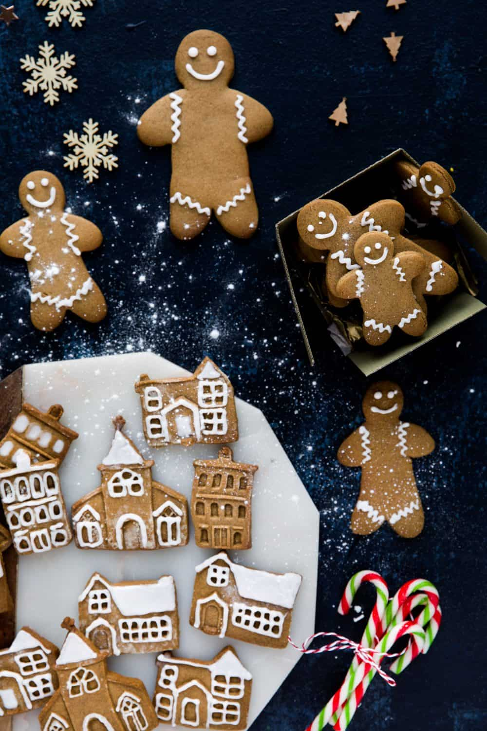 A selection of gingerbread houses, churches and gingerbread men laying on a dark blue background and sprinkled with icing sugar.