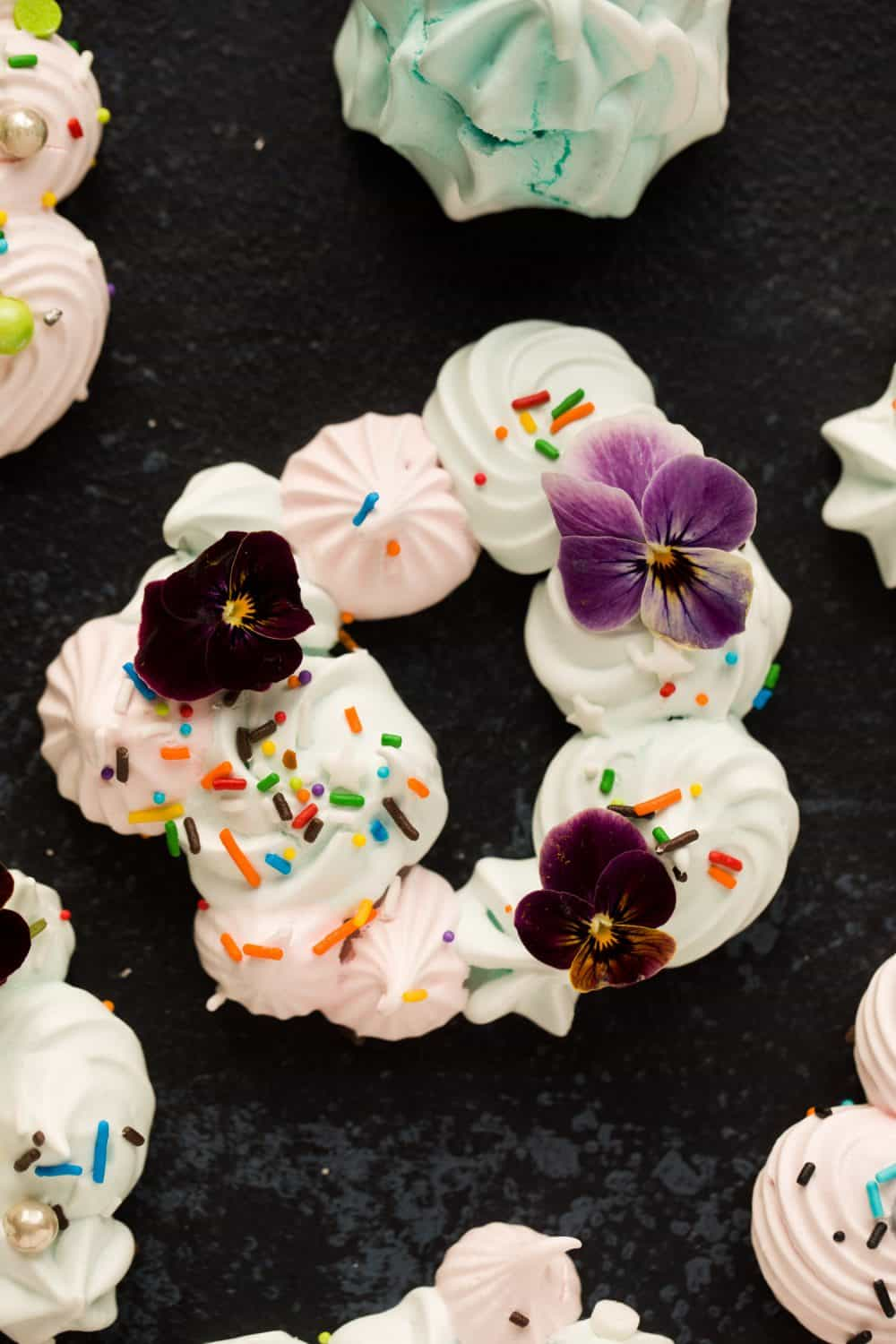 A small Christmas Meringue Wreath with edible flowers as decoration.