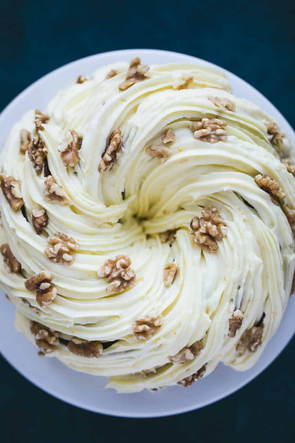 A carrot cake bundt cake covered in cream cheese frosting and walnuts.